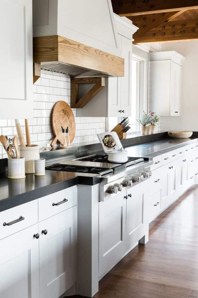 11 Best Kitchens by Studio McGee; This farmhouse style kitchen is bright and bold with dark countertops and clean white cabinets