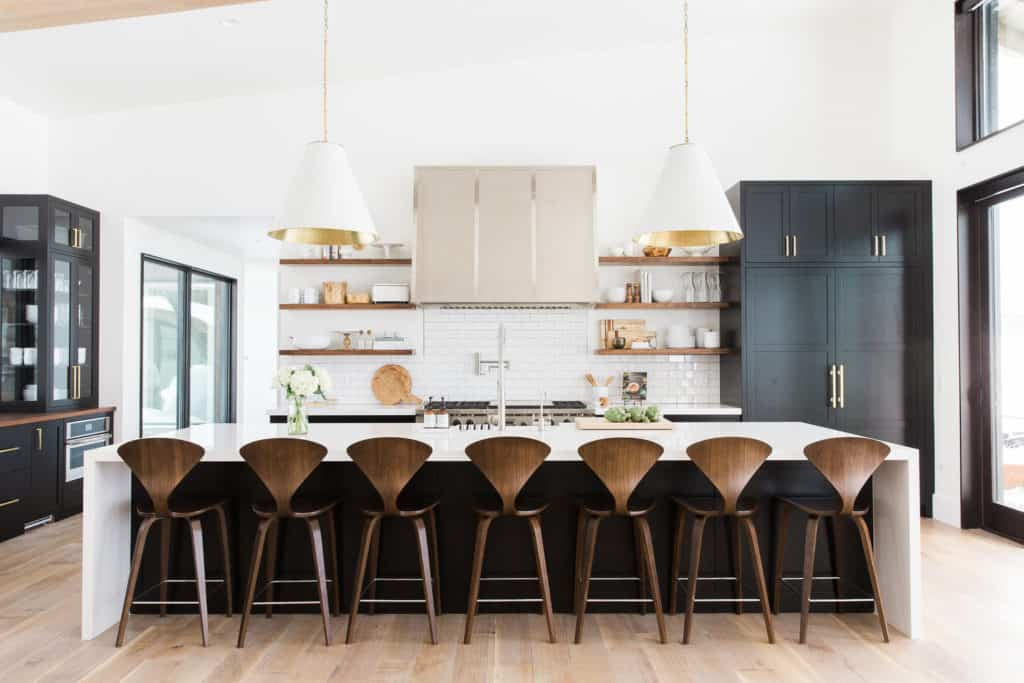 11 Best Kitchens by Studio McGee; This large kitchen makes a bold statement with black accents to complement the mostly white decor. I love the black cabinets and breakfast island!