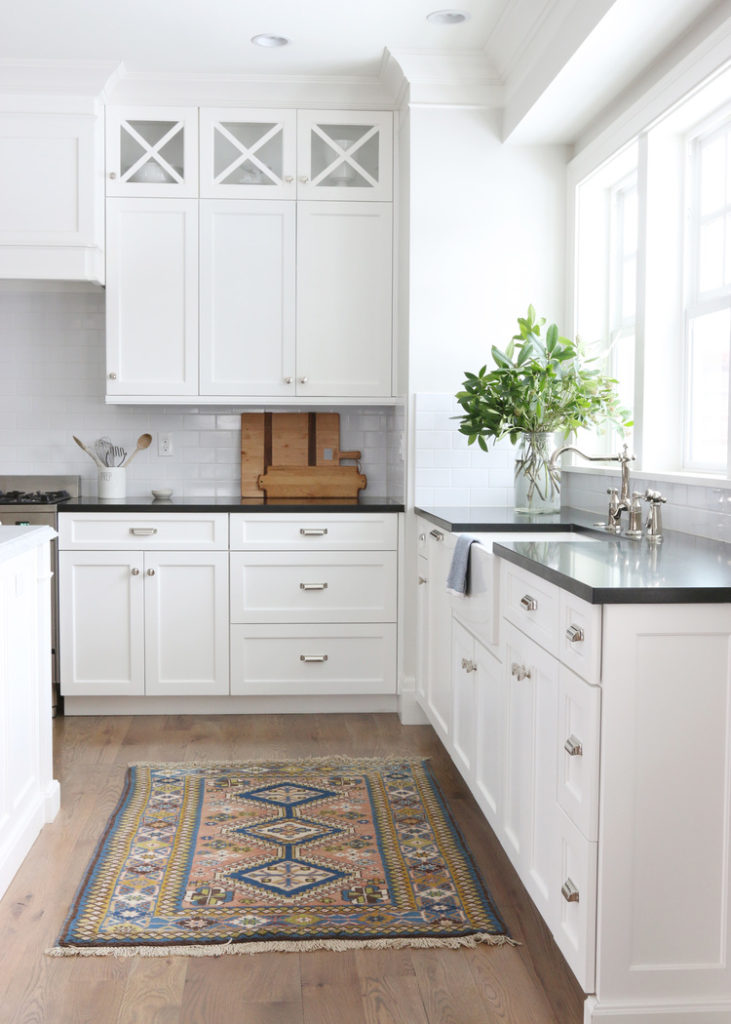 11 Best Kitchens by Studio McGee; the dark marble counter tops are a great accent with all-white cabinets and silver hardware