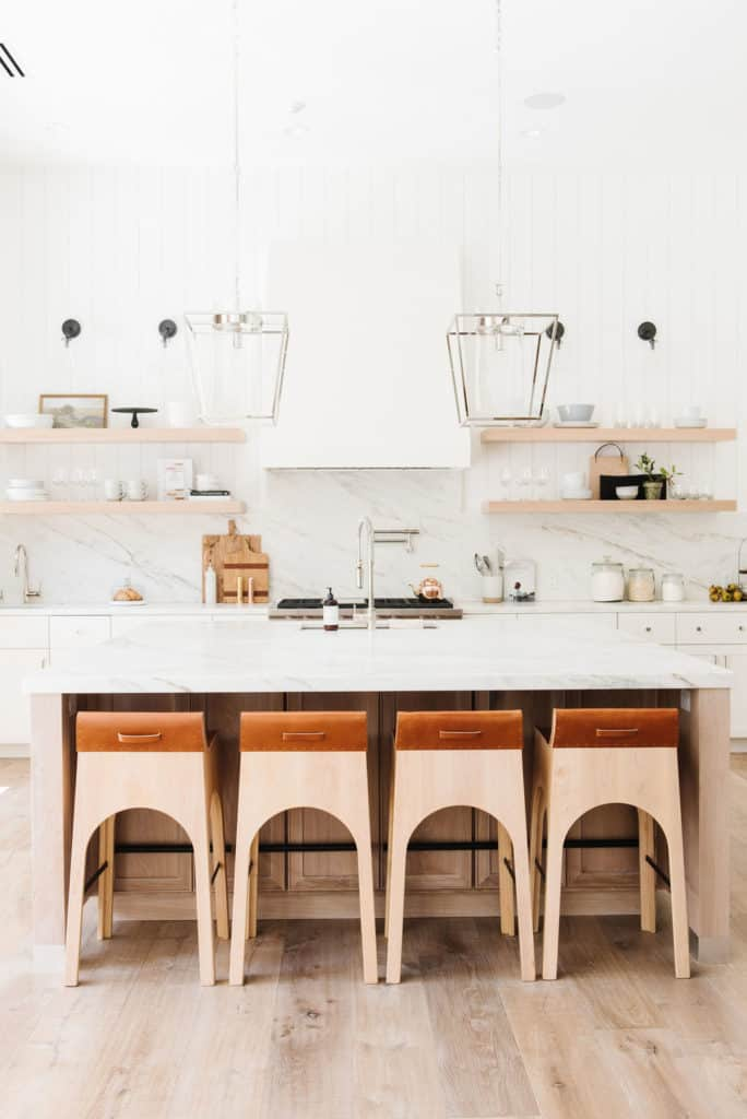 11 Best Kitchens by Studio McGee; This modern style lakehouse kitchen is so clean and bright! I love the marble backsplash and wooden breakfast bar chairs