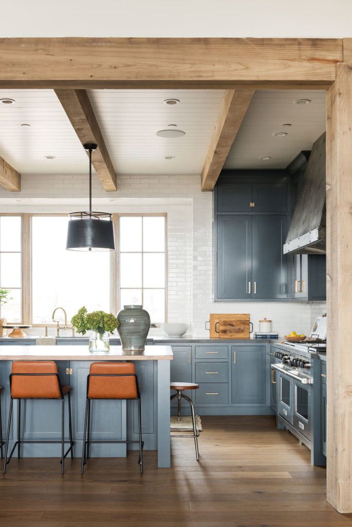 11 Best Kitchens by Studio McGee; This modern country style kitchen has gorgeous cobalt blue cabinets, which look great with the white brick backsplash