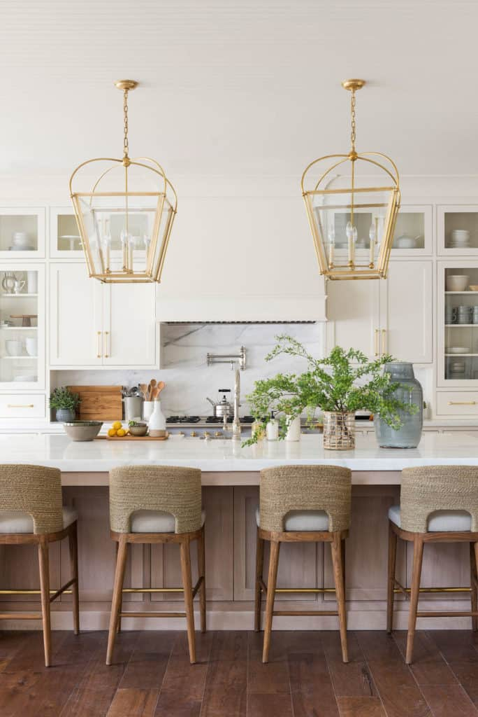 11 Best Kitchens by Studio McGee; These mordern industrial cage light fixtures go so well with the all-white color scheme of this kitchen. The breakfast bar chairs add color and texture!