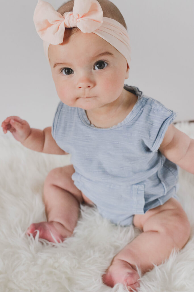 6 month old schedule - day in the life of a baby - infant girl with blue onesie and pink headband on. Baby photography