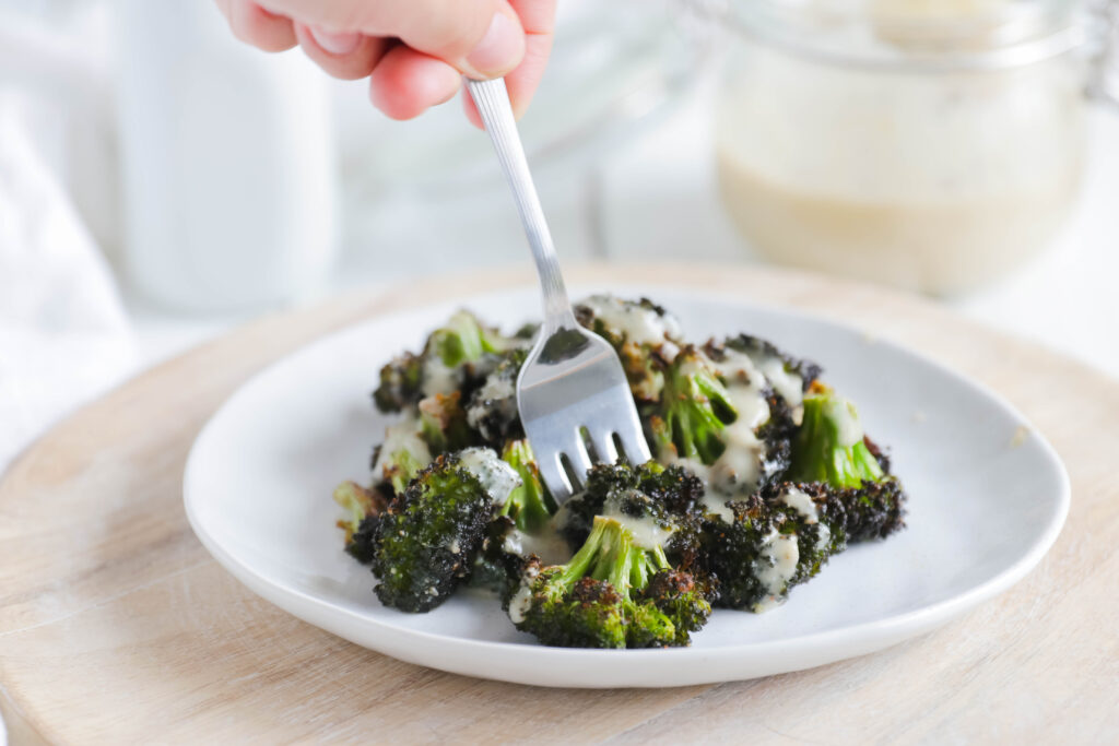 Fork eating Crispy Broccoli with Vegan Cheese Sauce; dairy and gluten free side dish for your vegan dinner! A nut free cheese sauce that you will love smothered on your blackened broccoli!
