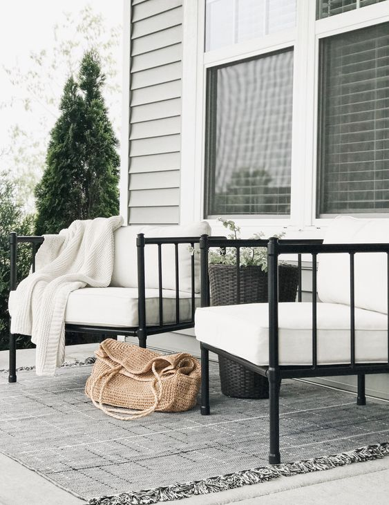 15 Deck Must Haves for Summer Entertaining; black iron rod outdoor chairs, white cushions, outdoor rug