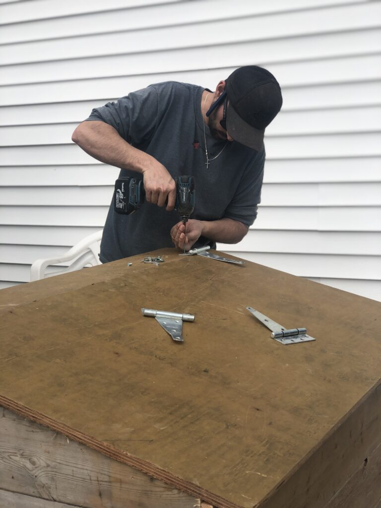 Drilling hinges onto outdoor garbage box lid for easy opening