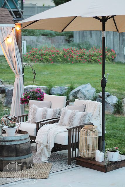 15 Deck Must Haves for Summer Entertaining; umbrella, comfy chairs with beige cushions, country farm decor