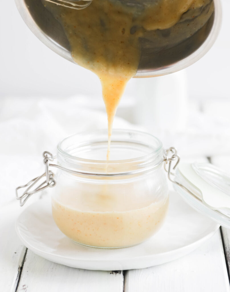 Sauce pot pouring white vegan cheese sauce into a air tight container