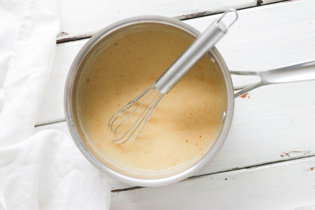 Sauce pot with whisk. White cheese sauce inside Vegan