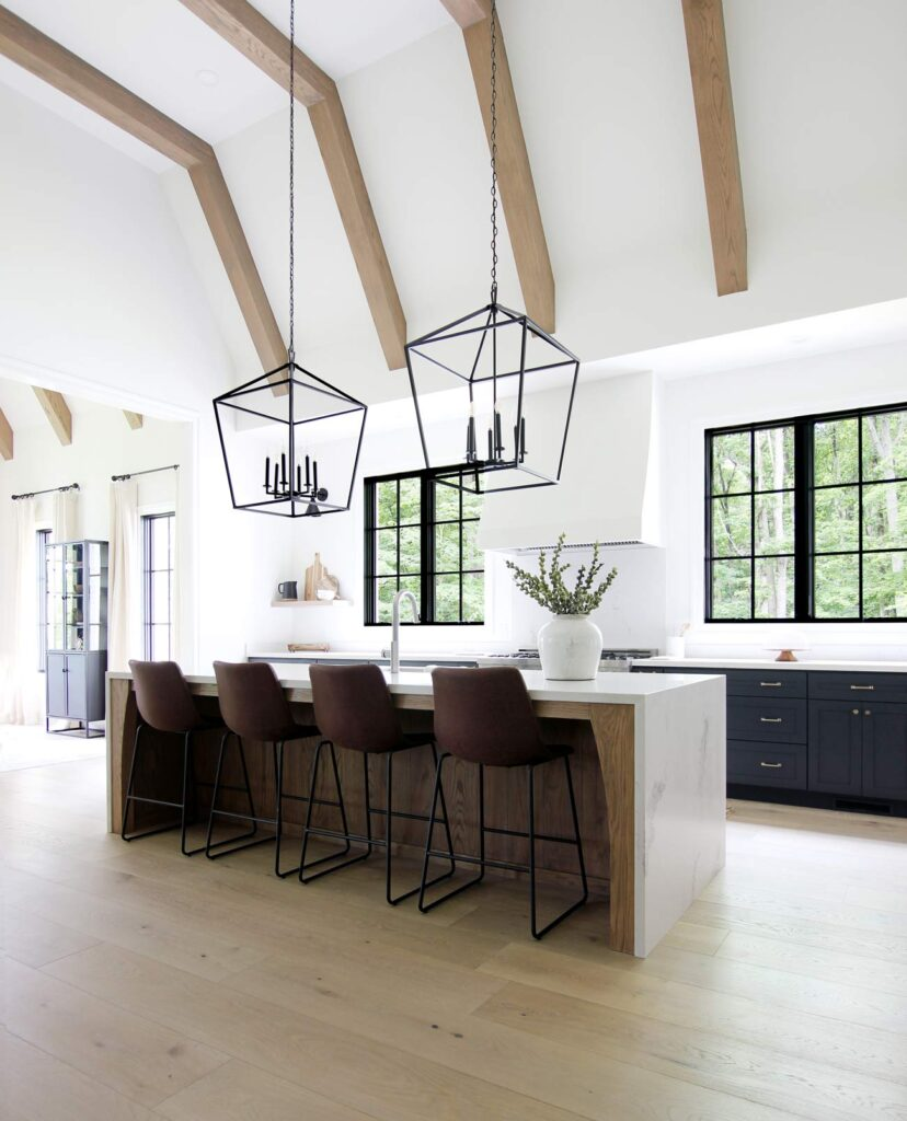 Best Home Decor Instagram Accounts You Should Be Following; White kitchen, leather barstools, large black pendents