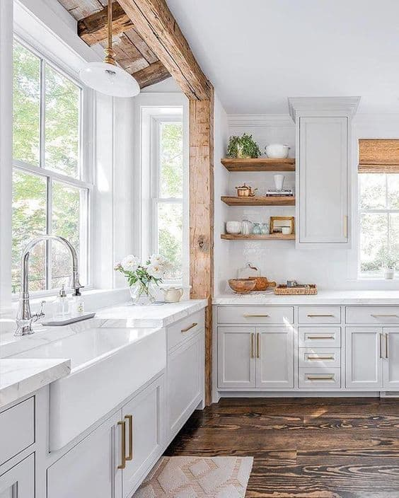 Tips for styling a farmhouse kitchen; white kitchen with wood beam. white farmhouse sink, open shelving in kitchen