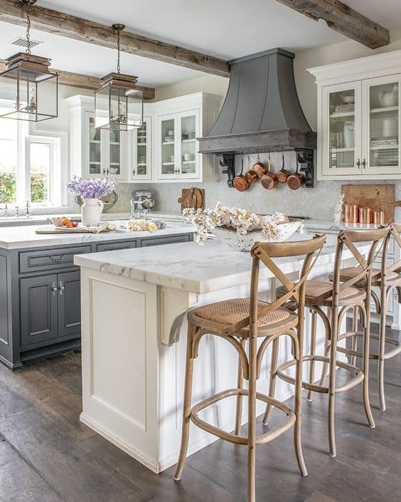 Tips for styling a farmhouse kitchen; wood barstools, dark oven, white cabinets, wood beams