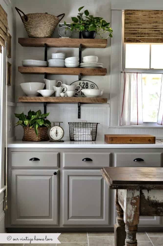 Tips for styling a farmhouse kitchen; grey cabinets, open shelving, wood in the kitchen, black kitchen hardware