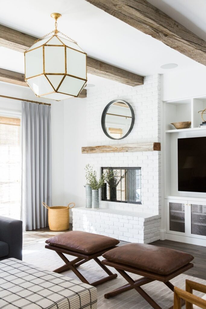 Studio Mcgee living room, white stone fireplace with round mirror and rustic mantel