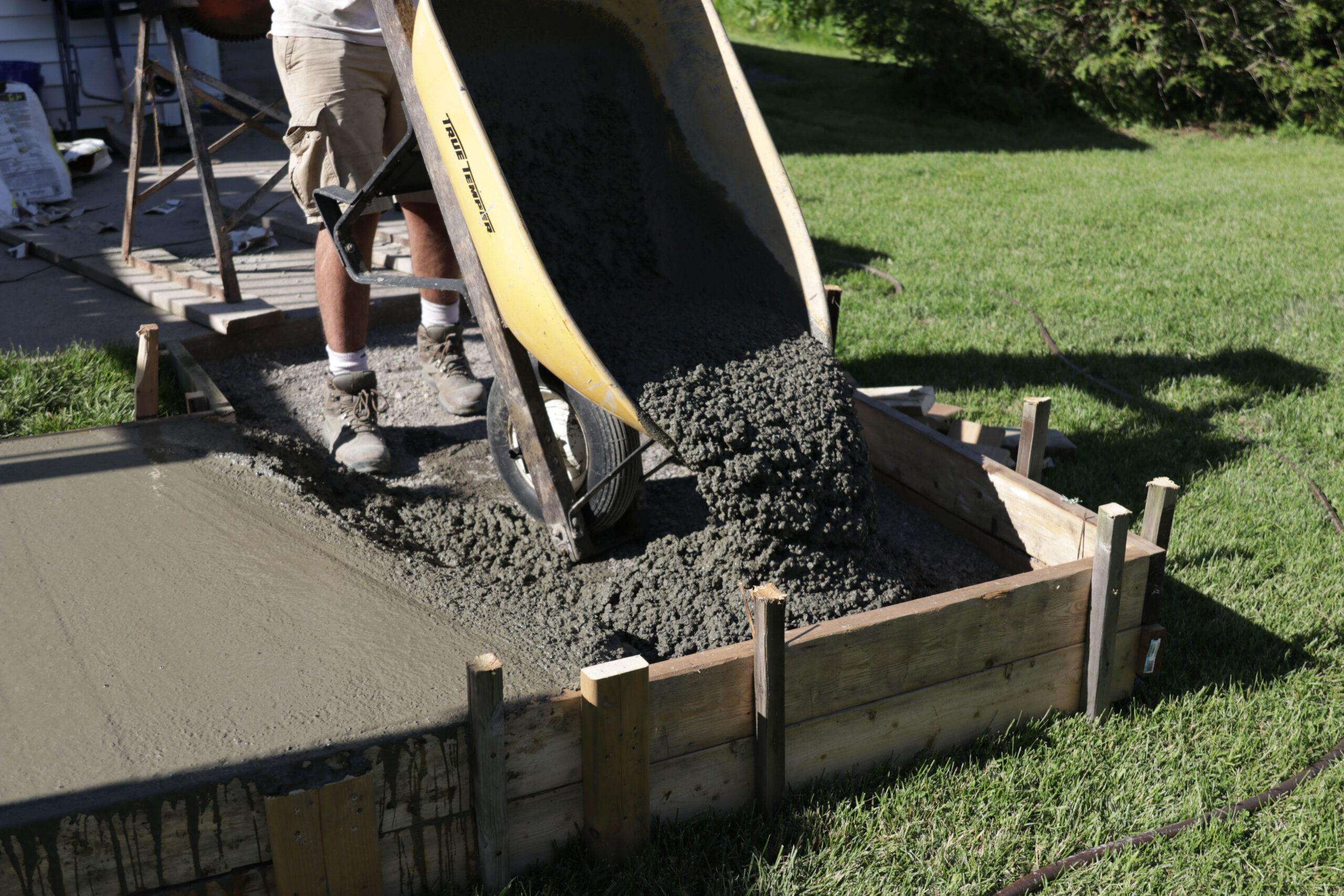 wheelbarrow pouring concrete for walkway