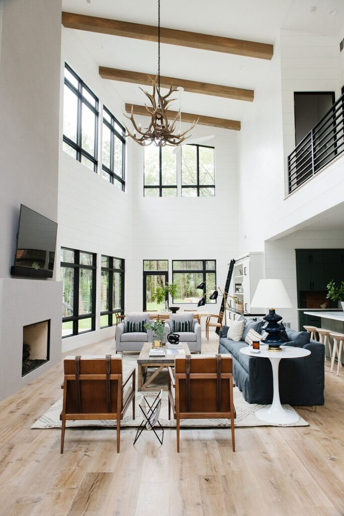 Studio Mcgee living room, open concept living room, rustic coffee table, navy couch, leather accent couch, large windows