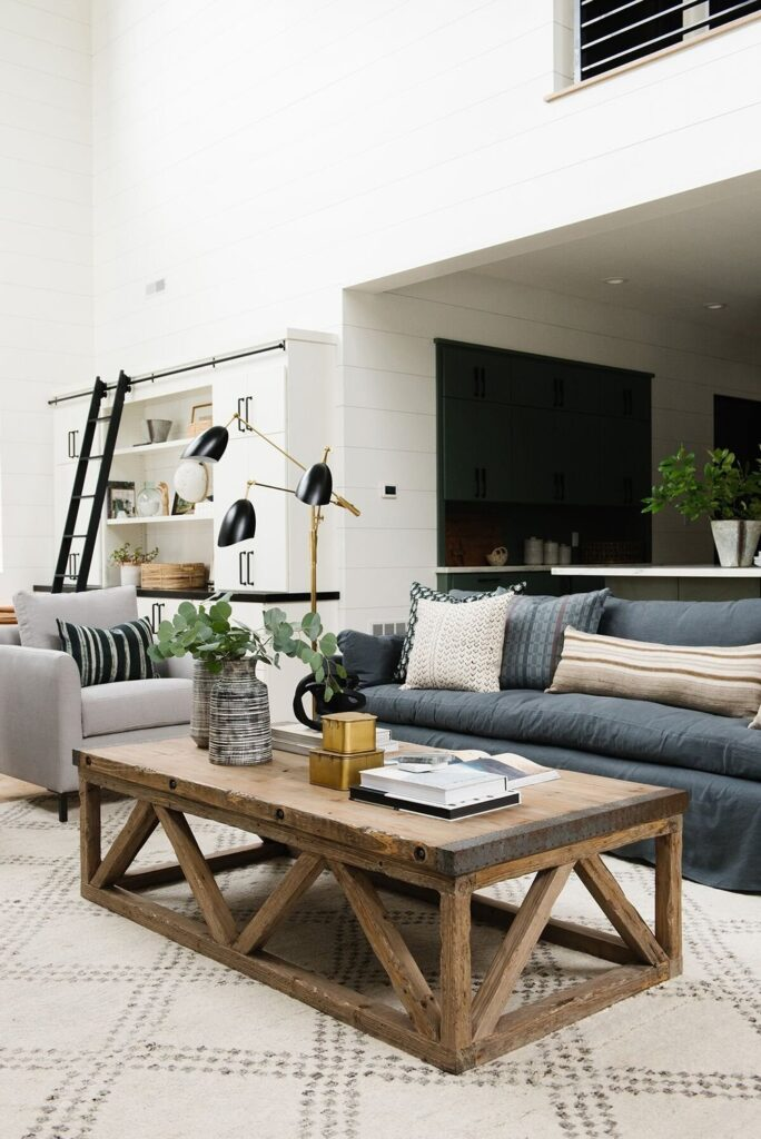 Studio Mcgee living room, open concept living room, rustic coffee table, navy couch