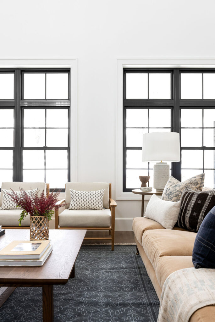 Studio Mcgee living room with beige couch, large black windows, warm tones, open living space