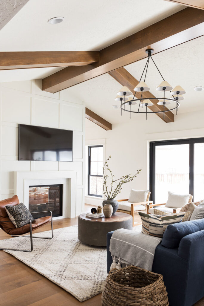 Studio Mcgee living room, white fireplace, circle chandelier, leather accent chair, two way fireplace
