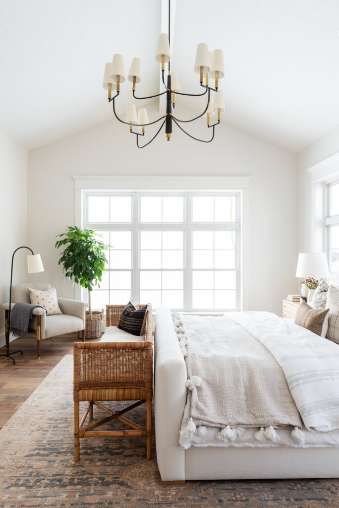 Studio McGee by Bedrooms: Studio McGee House; white walls, neutral colours, vaulted ceiling, large window, grey bed with white linen, wicker seating
