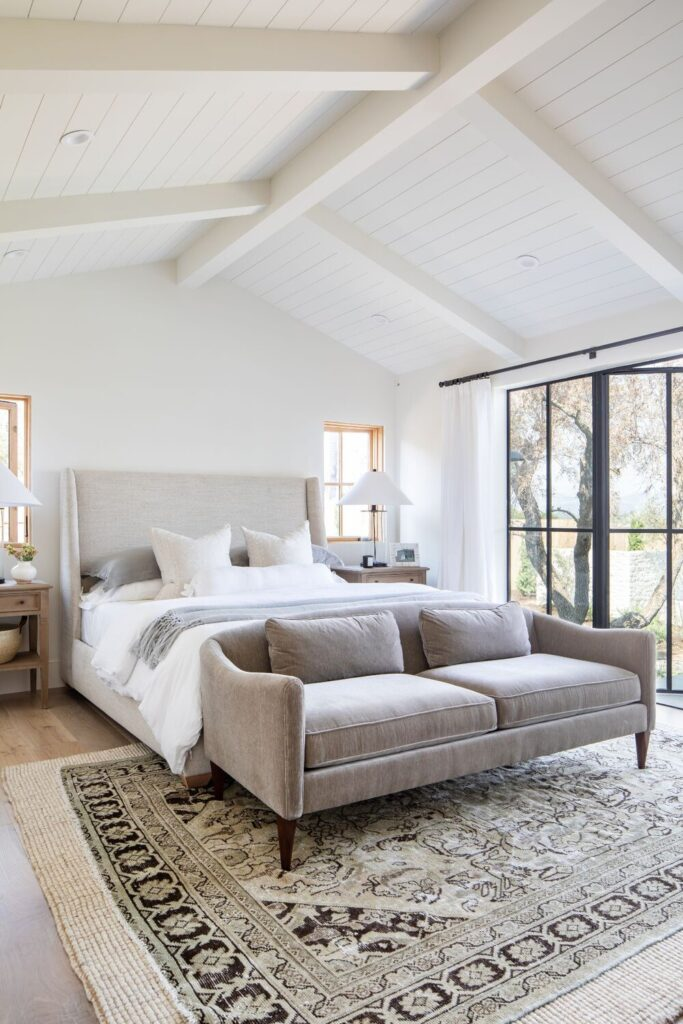Studio McGee by Bedrooms: The Crestview House; white walls, vaulted ceiling, grey bed with white linen, grey couch