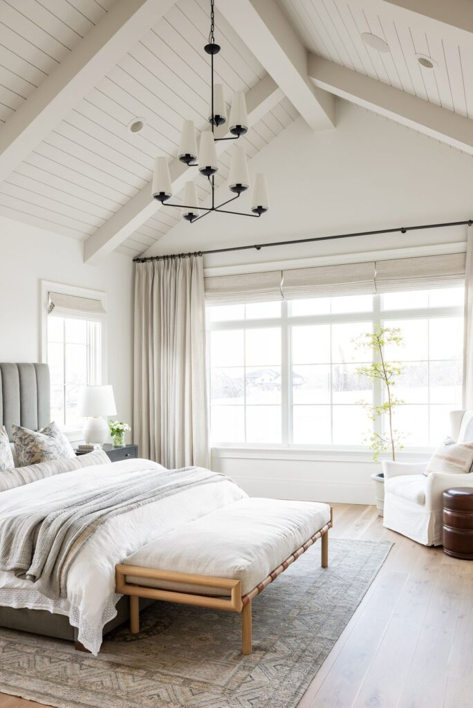 Studio McGee by Bedrooms: Studio McGee House; white walls, neutral colours, vaulted ceiling, large window, grey bed with white linen