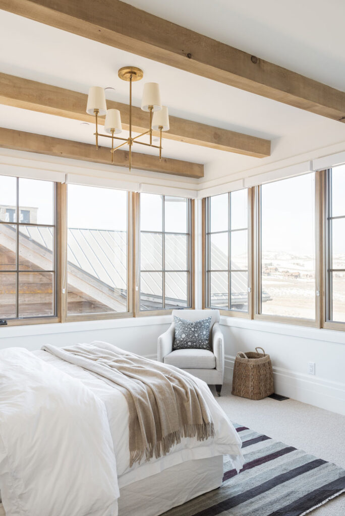 Studio McGee by Bedrooms: SM Ranch House; rustic beams white walls, natural bedding