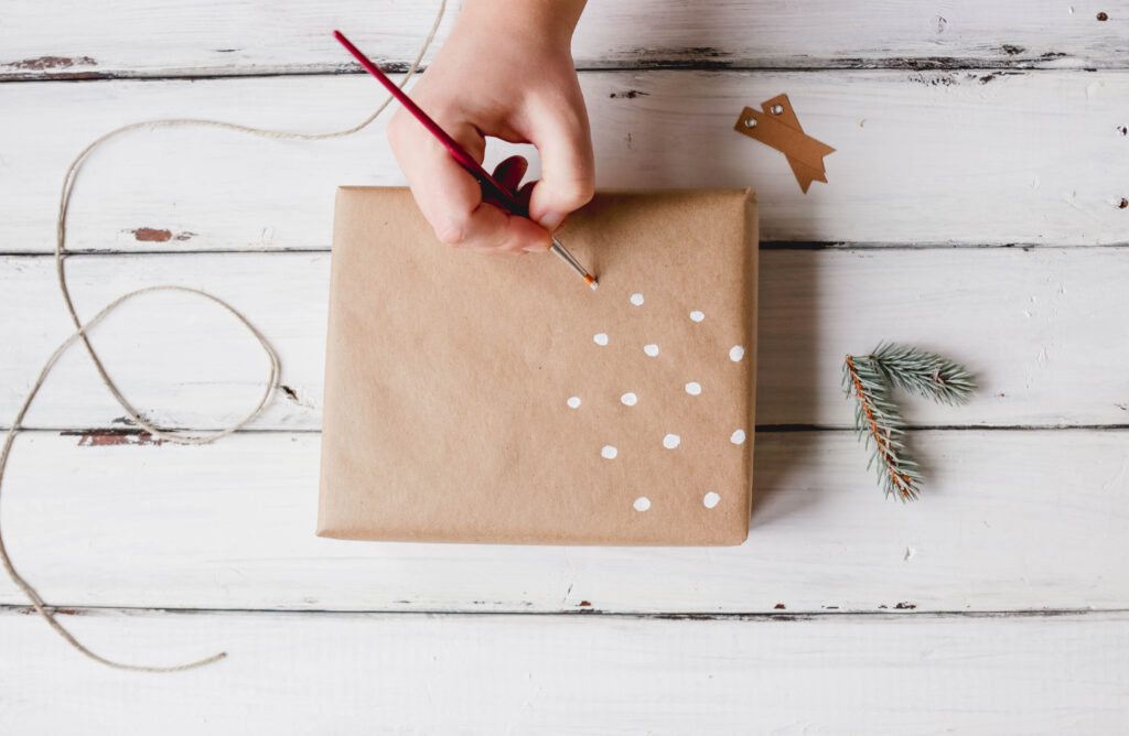 Painting white dots on rustic Christmas gift wrap