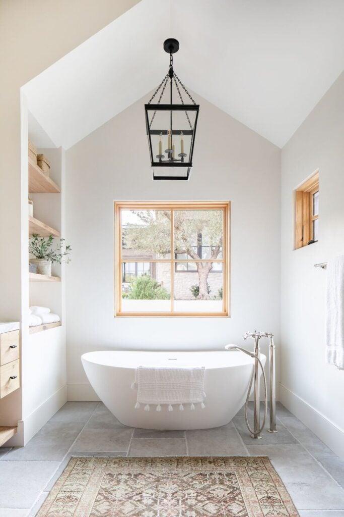 Studio McGee Bathrooms; white bathtub, vaulted ceiling, oak wood, black light