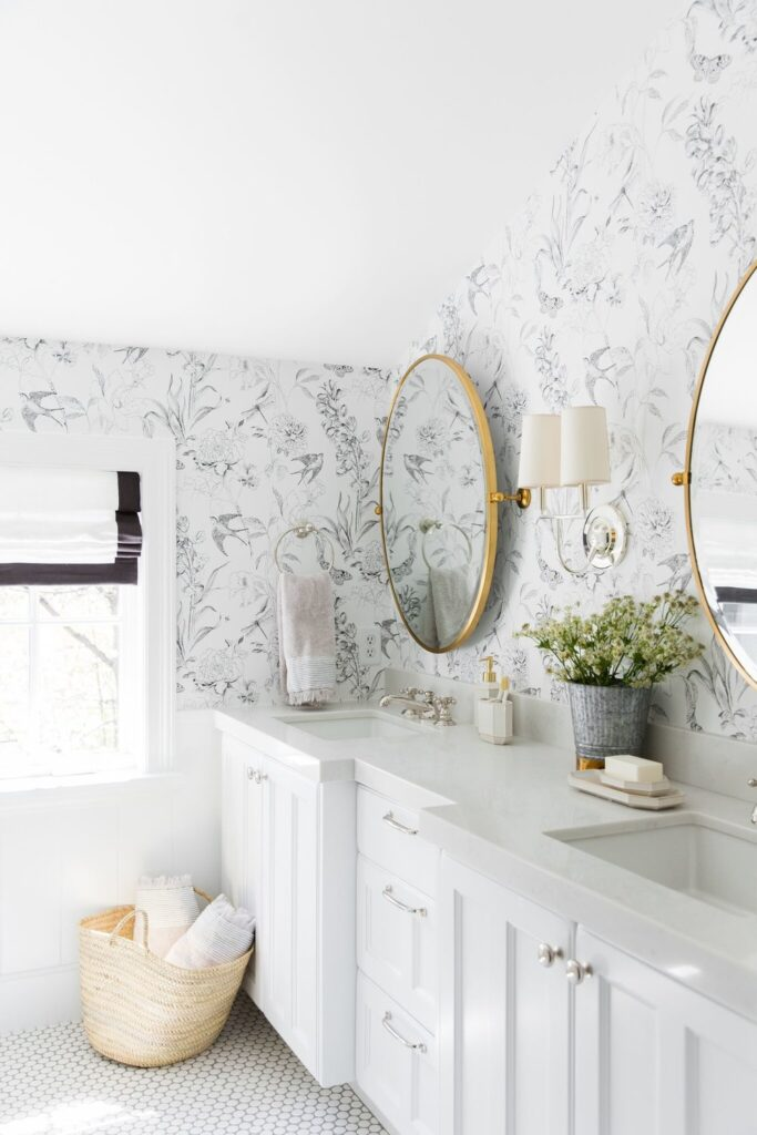 Bathrooms by Studio McGee; marble counter, white vanity, wallpaper in bathroom, gold mirror, slanted ceiling