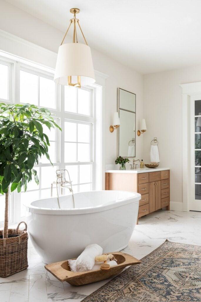 Bathrooms by Studio McGee; stand alone white bathtub, large window, greenery