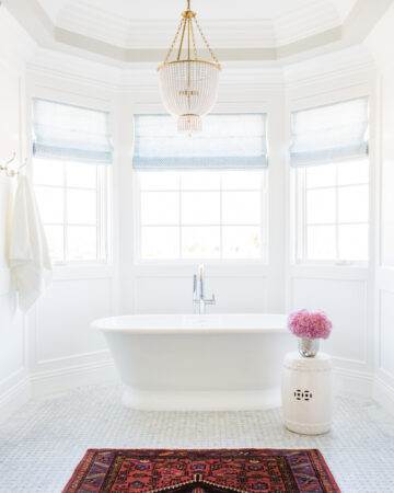 Bathrooms by Studio McGee; coastal bathroom, white tub, stand alone bathtub, chandelier