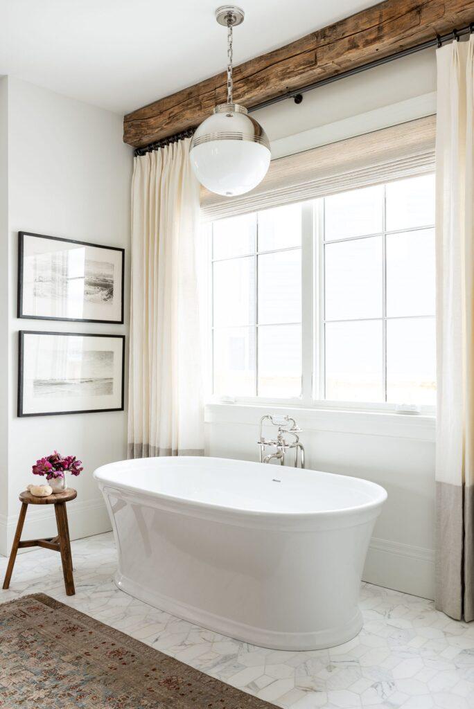 Studio McGee Bathrooms; white bathtub, wood beams, large window