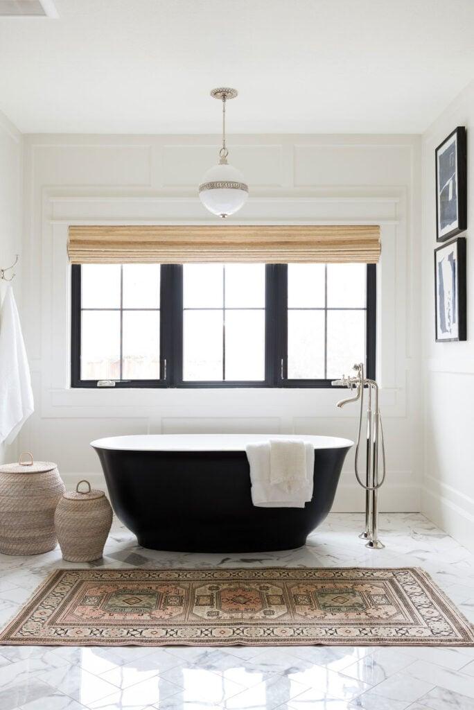 Bathrooms by Studio McGee; black tub, black stand alone bathtub, large window