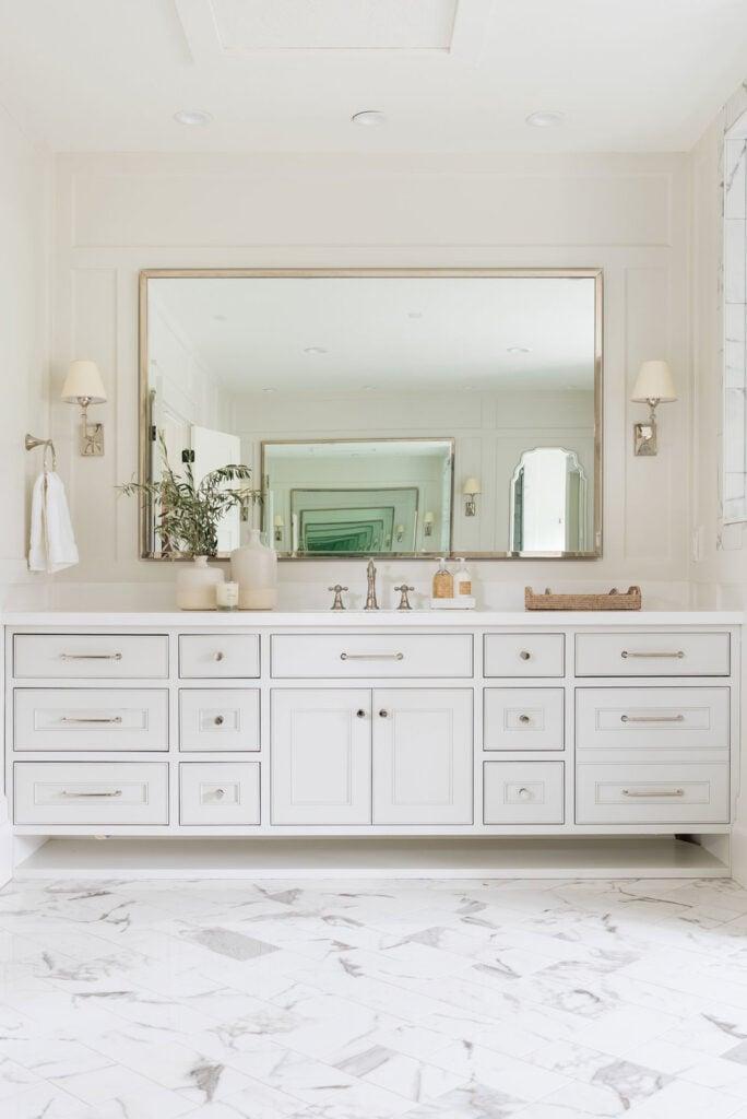 Bathrooms by Studio McGee; white vanity, large mirror, white bathroom