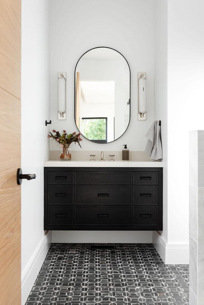 Studio McGee Bathrooms; black vanity, oval mirror, sconces