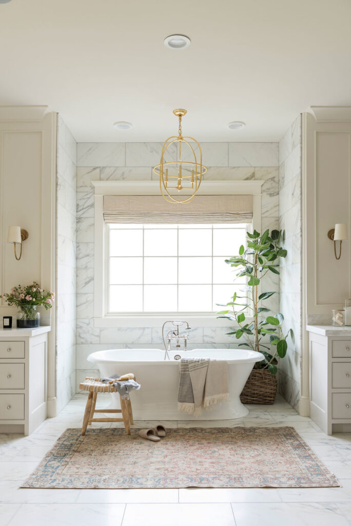 Bathrooms by Studio McGee; stand alone white tub, gold accents, greenery, large mirror