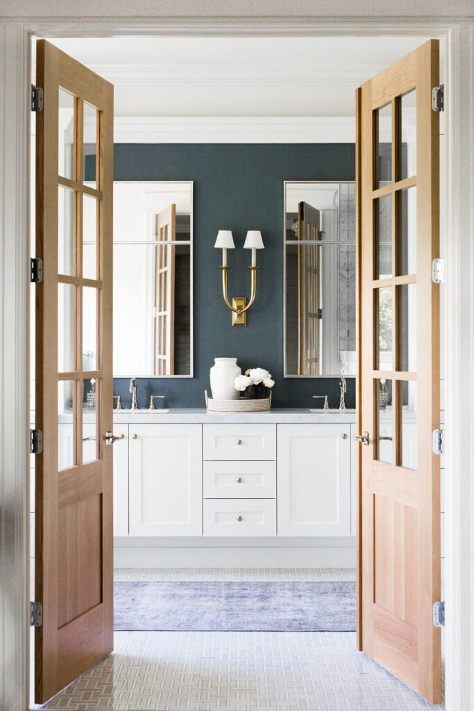 Bathrooms by Studio McGee; dark blue walls, gold accents, white vanity, marble counter tops