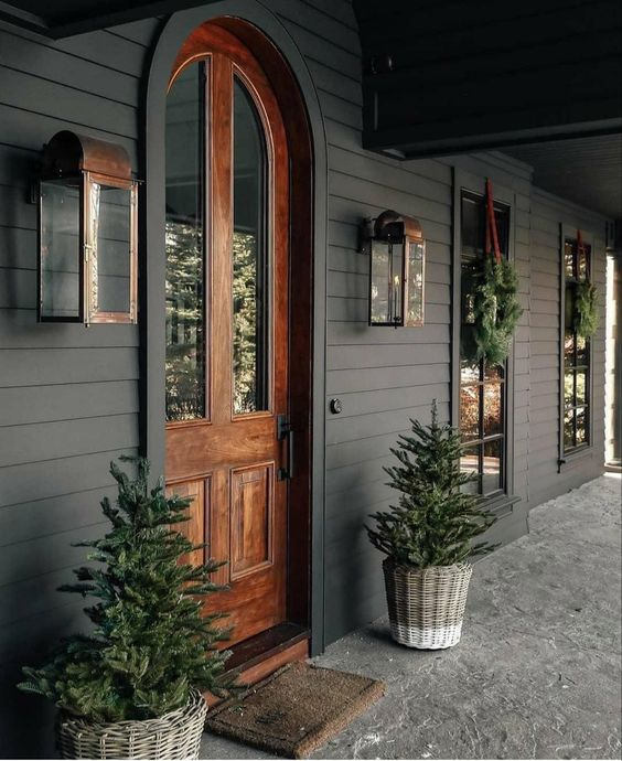 Modern Farmhouse Design Must haves: dark siding, wood door, front porch, large copper scones