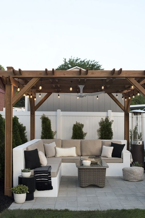Tips for Styling your Deck this Summer; gazebo with string lights, white fence, outdoor sectional