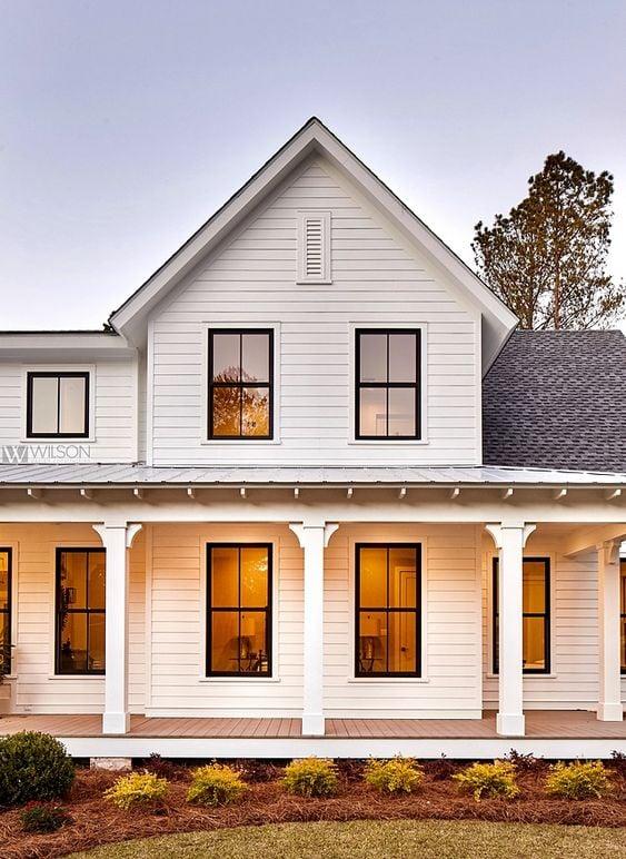Modern Farmhouse Design Must haves: front porch, sitting area, open porch, white siding, black windows