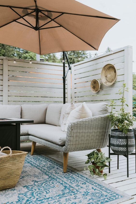 Tips for Styling your Deck this Summer; umbrella, privacy wall, beige cushions, beige couch, blue rug