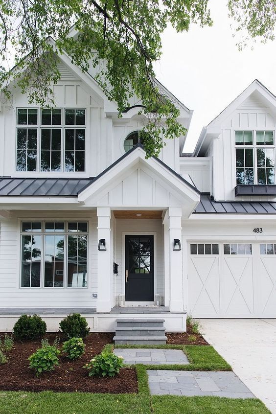 Modern Farmhouse Design Must haves: large windows, white siding, white garage door, black steel roof, white front porch