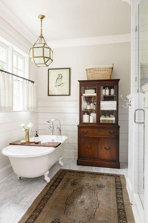 Modern Farmhouse Design Must haves: farmhouse bathroom, claw foot tub, white, wood linen cabinet, shiplap in bathrooms