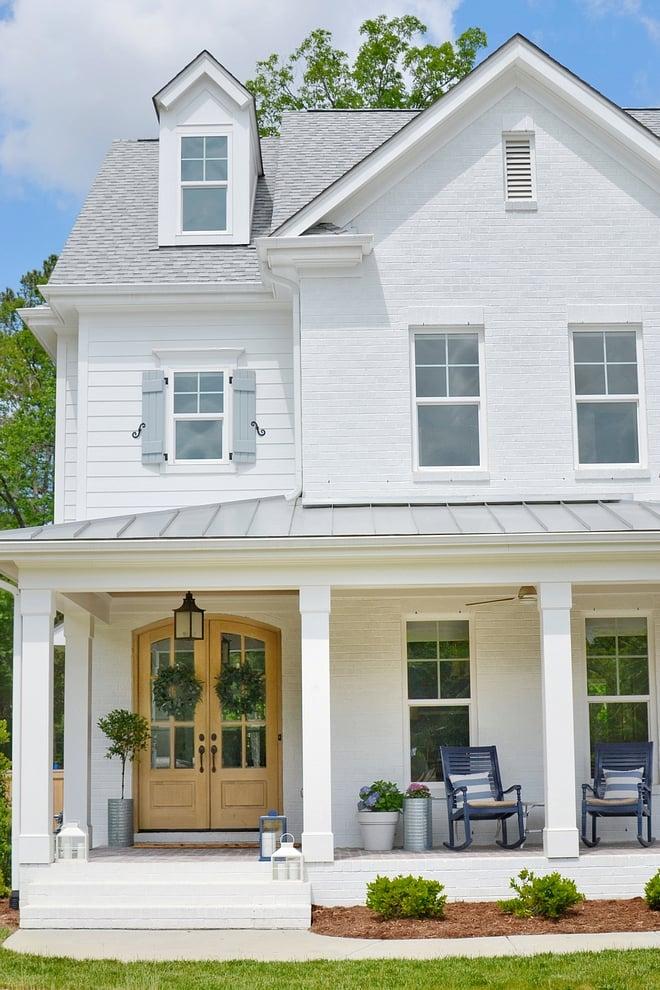 white modern farm house, white trim windows, large front porch, oak front door, porch rocking chairs