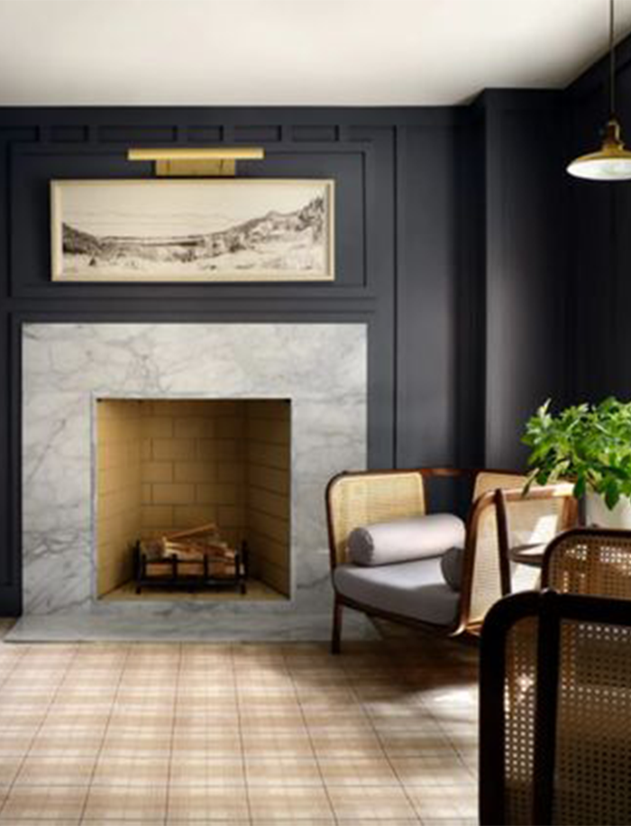 Best NEW Living Rooms by Joanna Gaines from Fixer Upper; navy walls, dark blue walls, marble fireplace, art above fireplace with gold light, wicker chairs seating