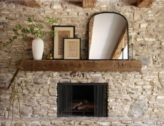 Best NEW Living Rooms by Joanna Gaines from Fixer Upper;  stone fireplace, rustic, wood beam, mirror, pictures, plant in vase